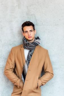 コートとスカーフを着てカメラを見ながら壁にもたれてトレンディな若い男の正面図