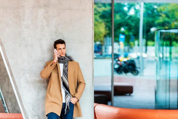 Вид спереди стильный молодой человек в джинсовой одежде, опираясь на стену при использовании мобильного телефона на открытом воздухе