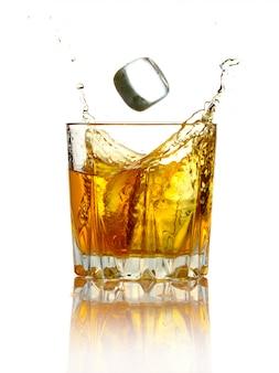 ガラスのウイスキーと分離された氷のしぶき