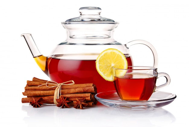 ティーポットと紅茶、スパイスと白で隔離されるレモンカップ