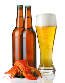 Бутылки и чашка светлого пива и куча омаров изолированы