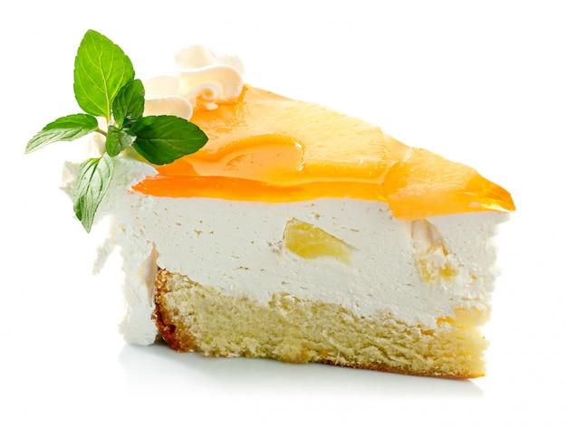 Кусочек торта с ананасовым кремом и листьями мяты изолированы