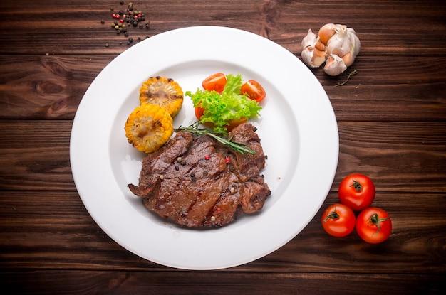 ビーフステーキ野菜と調味料の木製の背景