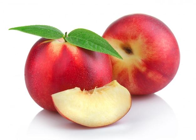 Спелые плоды персика (нектарина) с ломтиками изолированно