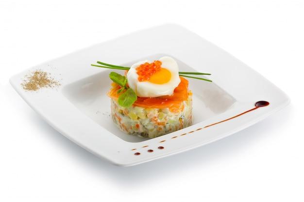 白い皿にサーモンステーキの地中海風サラダ