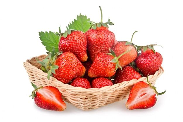白い背景で隔離の緑の葉と赤いイチゴ果実のバスケット
