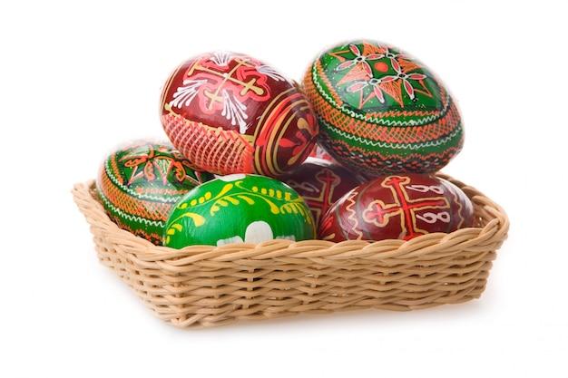 Группа цветных пасхальных яиц в корзине на белом фоне