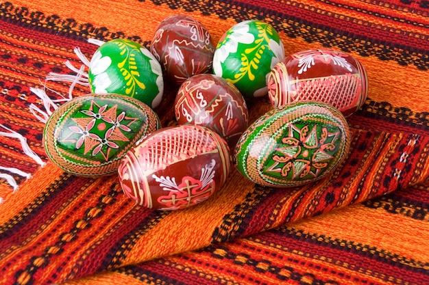 Куча разноцветных расписных пасхальных яиц на полотенце