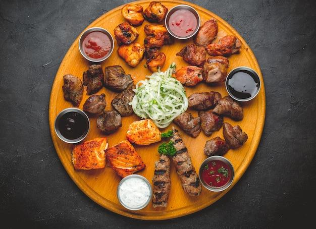 焼き肉と木製のテーブルのソースの盛り合わせ。