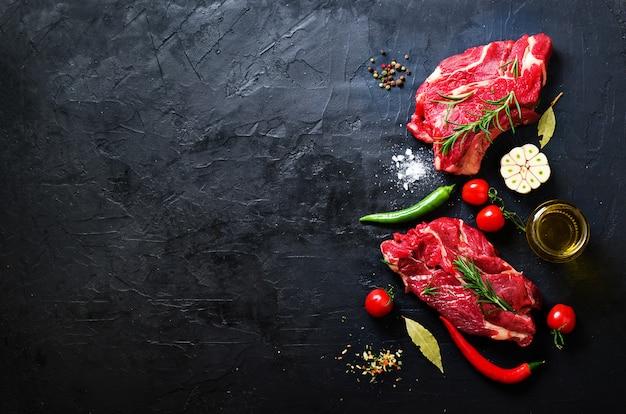 ハーブと石のまな板の上の生の肉ステーキ