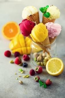 マンゴー、ライム、ミント、ピスタチオ、オレンジ、イチゴ、ラズベリー、ブルーベリー - さまざまな味のワッフルコーンのカラフルな赤、ピンク、黄色、緑、アイスクリームのボール。夏のコンセプト