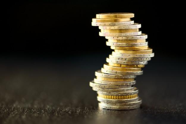 ユーロのお金、通貨。成功、富と貧困、貧困の概念ユーロ硬貨はコピースペースと濃い黒の上にスタックします。