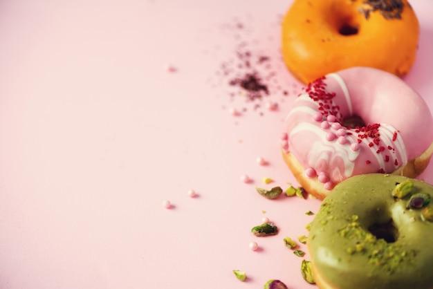 パステルピンクのアイシングとカラフルなドーナツ。ピスタチオ、チョコレートと甘いオレンジ、グリーン、ピンクのドーナツ。