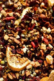 紅茶のカルカデとドライフルーツや花を混ぜるフルーツティーと質感。フード。有機性健康的なハーブの葉、デトックスティー。