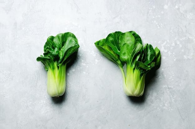 灰色のコンクリートの緑の有機チンゲン菜白菜。コピースペース、上面図、平干し