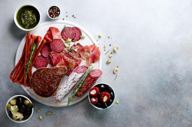 冷製スモークミートプレート。伝統的なイタリアの前菜、サラミ、生ハム、ハム、ポークチョップ、グレーのオリーブとまな板。平面図、コピースペース、平干し