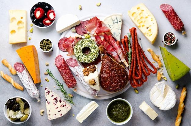 Традиционный итальянский антипасто, разделочная доска с салями, мясо холодного копчения, прошутто, ветчина, сыры, оливки, каперсы на сером.