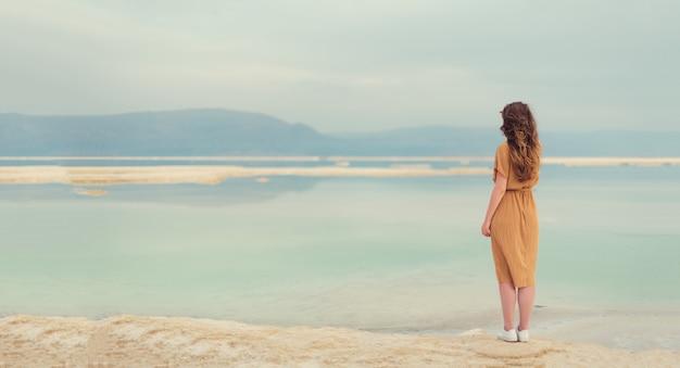海辺にドレスを着ているスタイリッシュな女の子の背面図