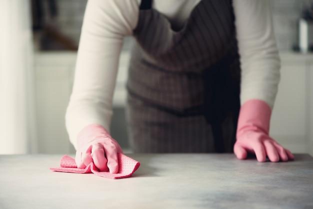 ほこりや汚れを拭くピンクのゴム製保護手袋の女。クリーニングコンセプト、コピースペース
