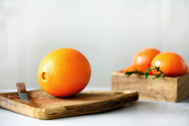 Цитрусовые. свежие фрукты, розмарин. большой апельсин с каплями воды, нож, деревянная разделочная доска