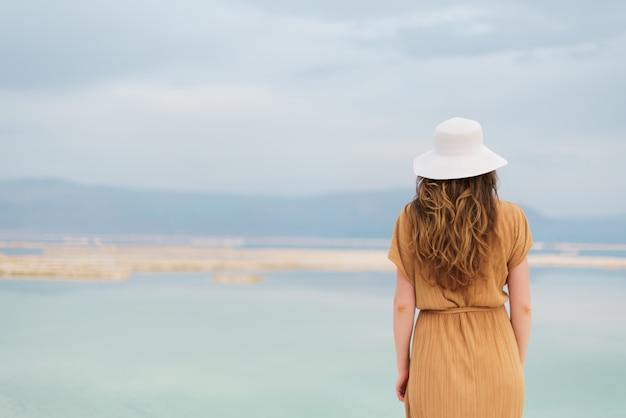 輝くブロンドの髪を持つ若い女の子が海辺に行きます