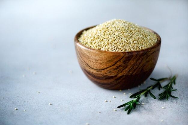 木製のボウルとグレーのローズマリーの生有機キノア。健康食品の成分コピースペース