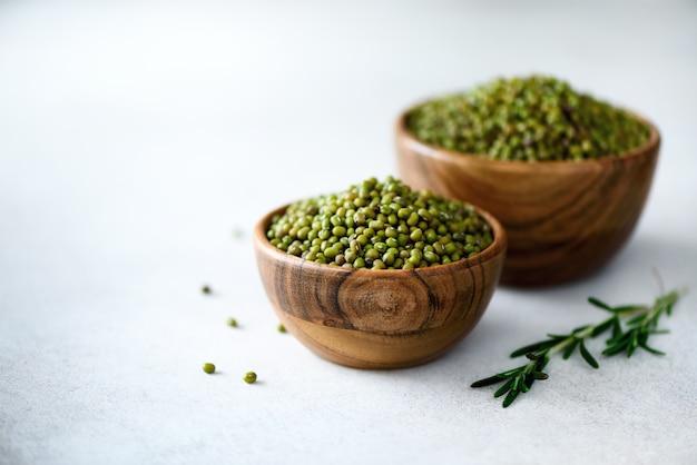 Бобы мунг, зеленая винья радиата в деревянной миске и розмарин на сером. копировать пространство