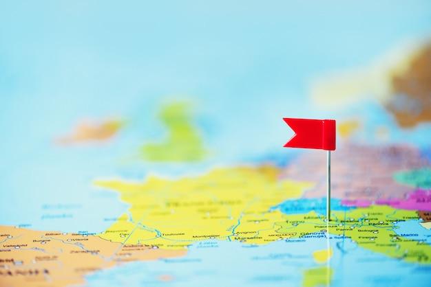 Красный флаг, канцелярская кнопка, канцелярская кнопка закреплена на карте европы. копирование пространства, концепция путешествия