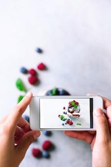 Девушка фотографирует завтрак, пудинг цзя с ягодами на мобильный телефон.