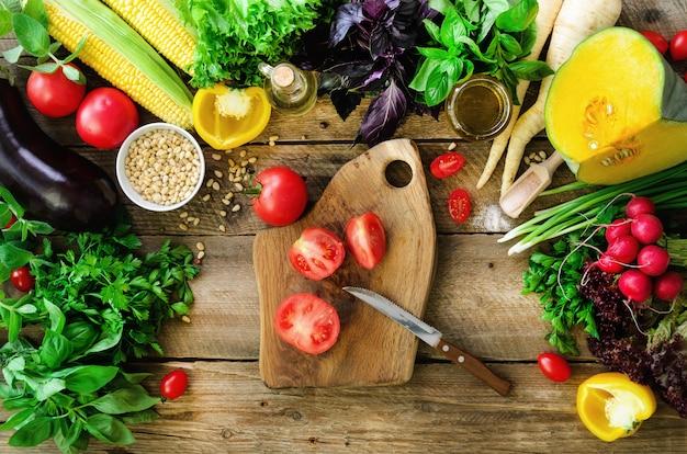 女性の手が木製の背景に野菜を切る。野菜料理の食材