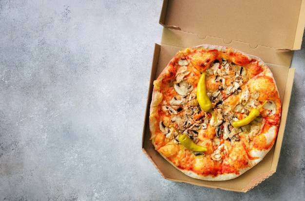 灰色のコンクリート背景に配達用ボックスで新鮮なピザ。上面図、コピースペース