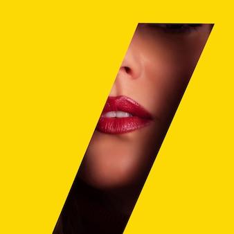 Девушка с ярким макияжем через отверстие в желтой бумаге