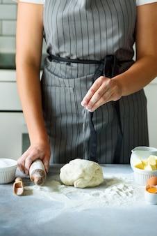 Женские руки замешивать тесто, выпечки фон. кулинарные ингредиенты
