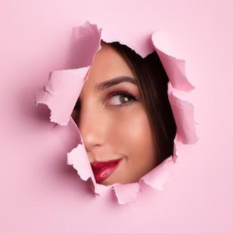 美しい少女は、ピンクの紙の背景の穴を通して見えます。
