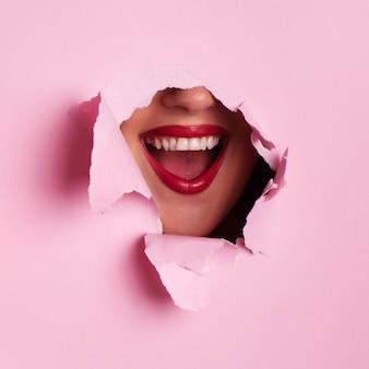 引き裂かれたピンクの紙の背景を通して真っ赤な唇。驚いた少女、感情。
