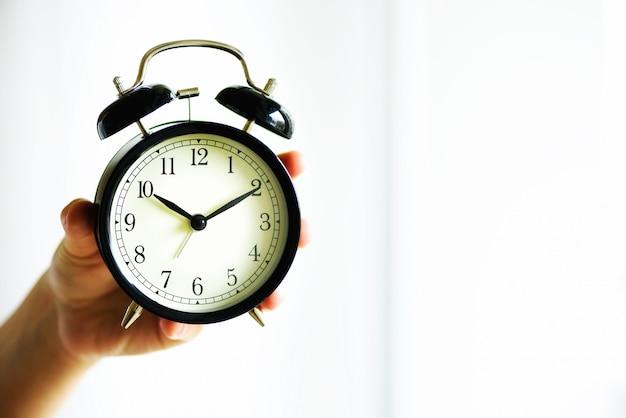 手に古典的な黒い目覚まし時計。晴れた朝の光。スペースをコピーします。