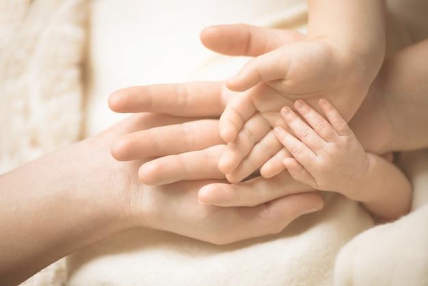 生まれたばかりの子供の手。両親の手に赤ちゃんの手のクローズアップ。家族、出産、出産のコンセプトです。