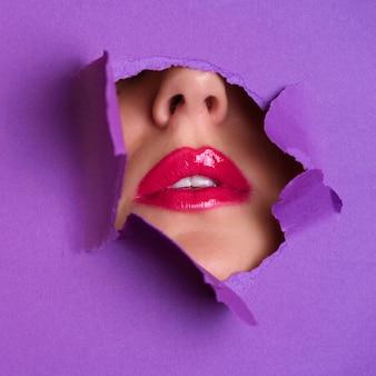 紫の紙の背景の穴を通して明るい唇の眺め。