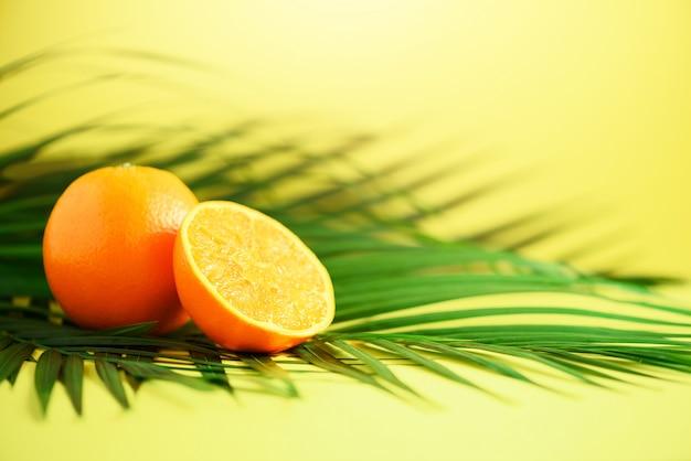 熱帯の緑のヤシの上のオレンジ色の果物は黄色の背景に残します。ポップアートデザイン、創造的な夏のコンセプト。