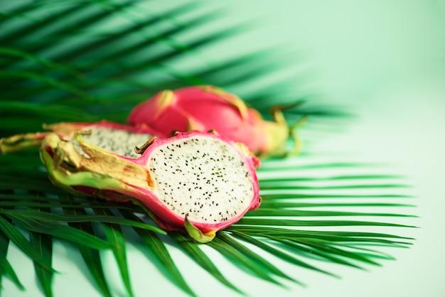 熱帯の緑のヤシの上のピタハヤやドラゴンフルーツはターコイズブルーの背景に残します。