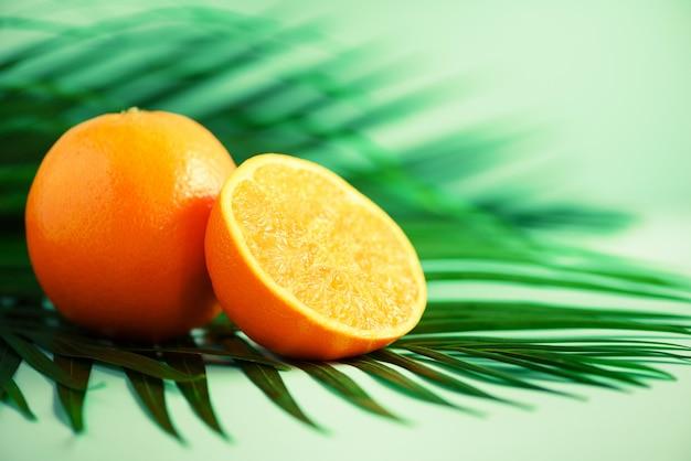 熱帯の緑のヤシの上のオレンジ色の果物は、青緑色の背景に残します。スペースをコピーします。ポップアートデザイン、創造的な夏のコンセプト。