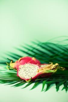 熱帯の緑のヤシの上のピタハヤやドラゴンフルーツはターコイズブルーの背景に残します。ポップアートデザイン、創造的な夏のコンセプト。