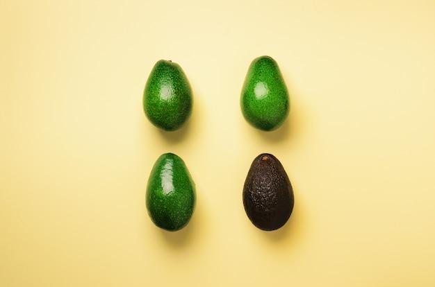 黄色の背景に有機アボカドパターン。最小限の平らなレイアウトスタイルの若い緑と黒の古いアボカド。
