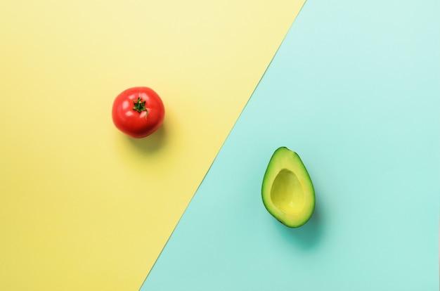 有機アボカド、青と黄色の背景にトマト。最小限の平らなレイアウトスタイルで野菜のパターン。