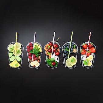 スムージーの食材と一緒に塗られたガラス、黒い黒板に飲み物