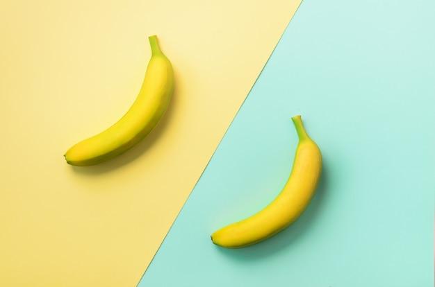 青と黄色の背景の上のバナナ。コピースペースとカラフルなフルーツパターン。最小限の平らなレイアウトスタイルのバナナ。