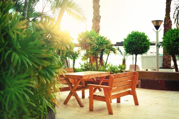 ビーチの歩道に空のベンチ。日当たりの良い休憩所。熱帯の緑のヤシの木の背景。太陽光効果と日当たりの良いボケ味。