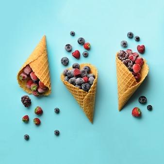 Замороженные ягоды - клубника, черника, ежевика, малина в вафельных рожков на синем фоне.