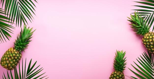 Ананасы и тропические пальмы листья на фоне резких пастельных розовых. летняя концепция.