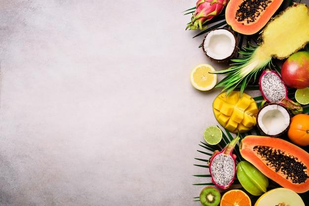 エキゾチックなフルーツと熱帯のヤシの葉 - パパイヤ、マンゴー、パイナップル、バナナ、カランボラ、ドラゴンフルーツ、キウイ、レモン、オレンジ、メロン、ココナッツ、ライム。
